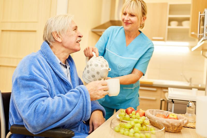 Senior man and caregiver at breakfast. Senior men and caregiver having breakfast with coffee pot in assisted living stock photo