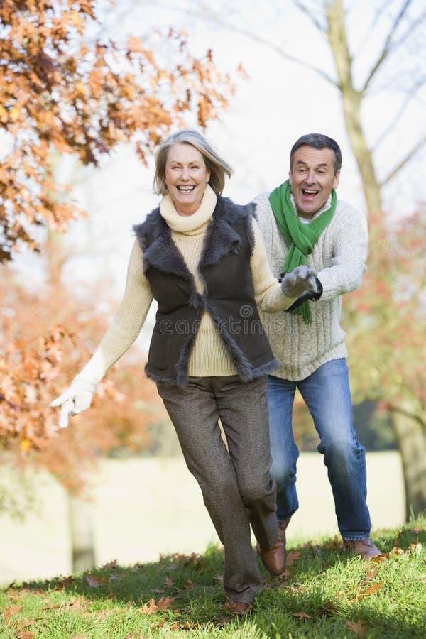 Senior man chasing woman through countryside stock photo