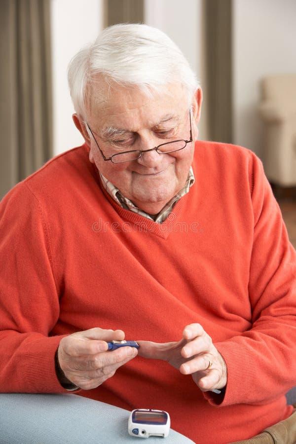 Senior Man Checking Blood Sugar Level. At Home royalty free stock photo