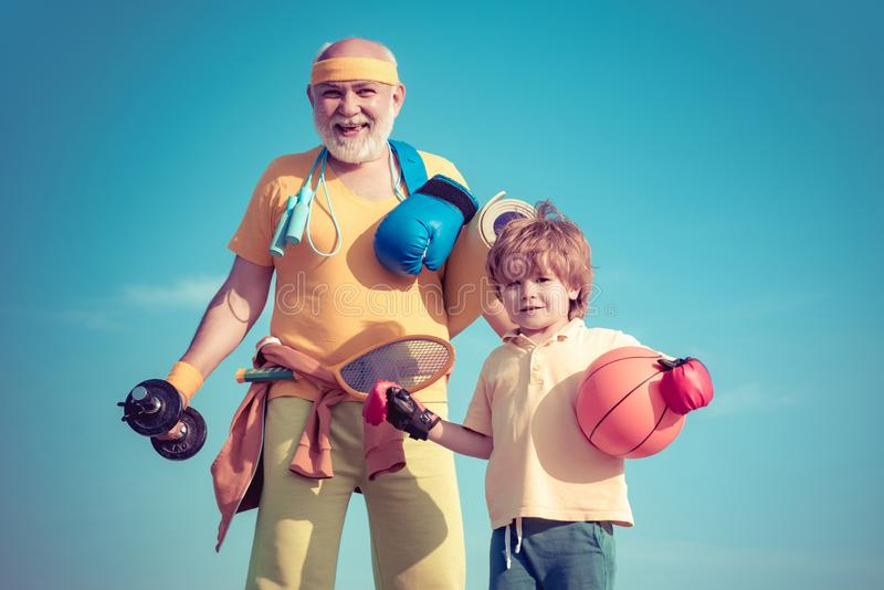 Senior man and child exercising on blue sky. Sport exercise for kids. Portrait of a healthy father and son working out. Senior men and child exercising on blue royalty free stock images