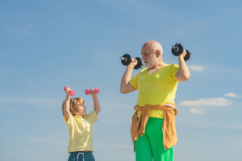 Senior man and child in family health club. Sportsman grandfather and healthy kid with dumbbell exercise. Grandfather royalty free stock image