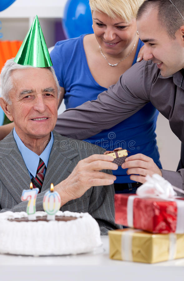 Senior man with children on birthday. Senior father with children celebrating 70th birthday royalty free stock photo