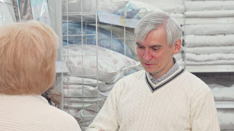 Senior man choosing bedding goods with his wife at furnishings store. Senior men choosing bedding goods with his wife at furnishings store. Elderly male customer stock image