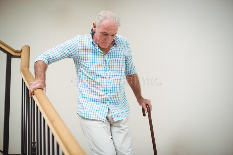 Senior man climbing downstairs with walking stick. At home royalty free stock photo