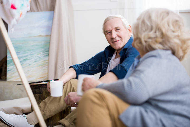 Senior man with coffee cup looking at wife royalty free stock image
