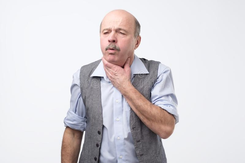 Senior man coughing being ill. Studio shoot. stock images