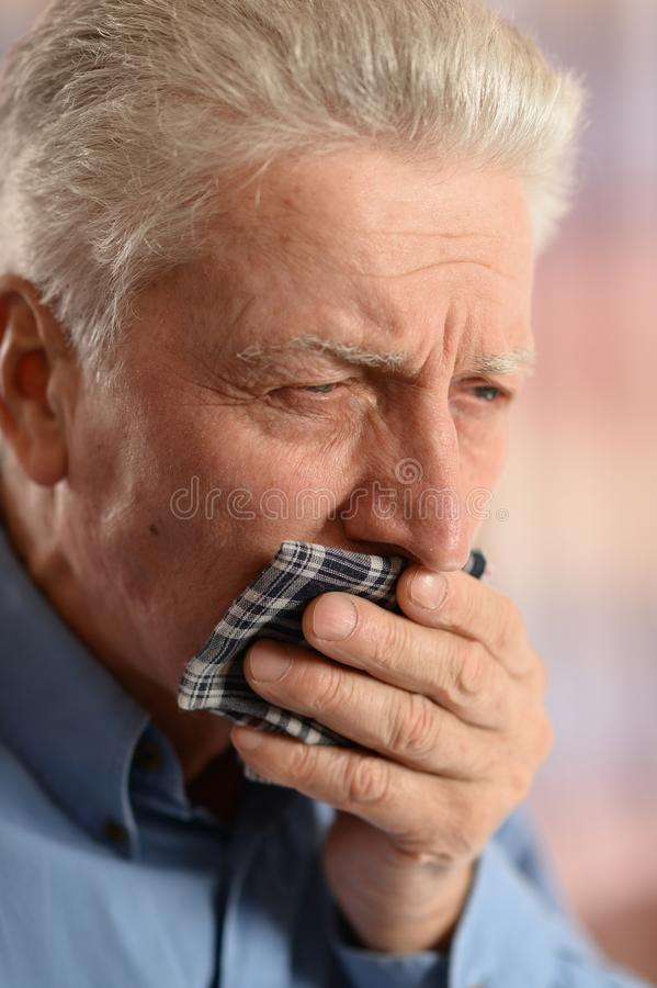Senior man coughing. Portrait of senior man with handkerchief coughing royalty free stock photo