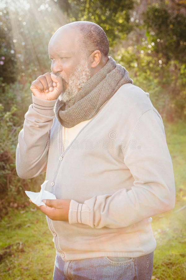 Senior man coughing with tissue stock photos