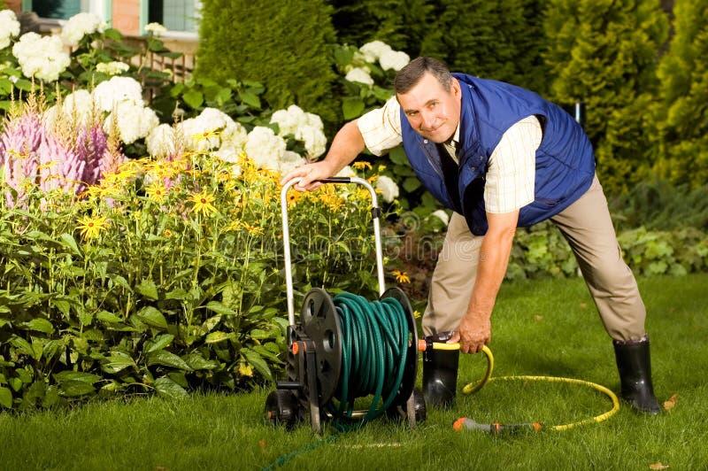 Senior man crimping hose in the garden royalty free stock photography