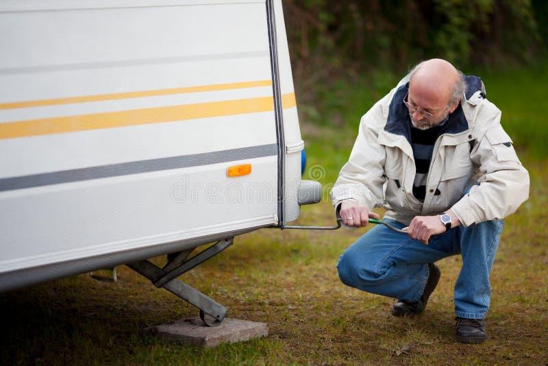 Senior Man Crouching While Repairing Caravan stock image