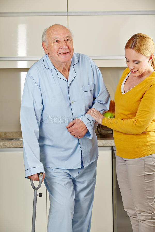 Senior man with crutches getting. Senior men with crutches in the kitchen getting help from eldercare assistant stock photo