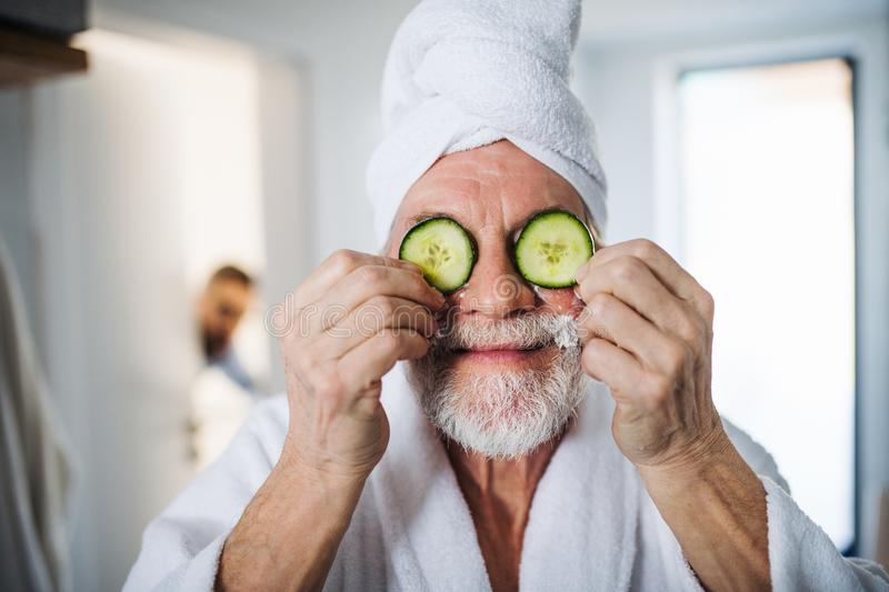 Senior man with cucumber on front of his eyes in bathroom indoors at home. royalty free stock images