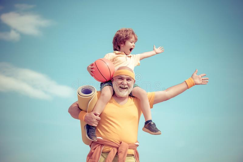 Senior man and cute little boy exercising on blue sky background - isolated. Father and son sporting - family time. Senior men and cute little boy exercising on stock photography