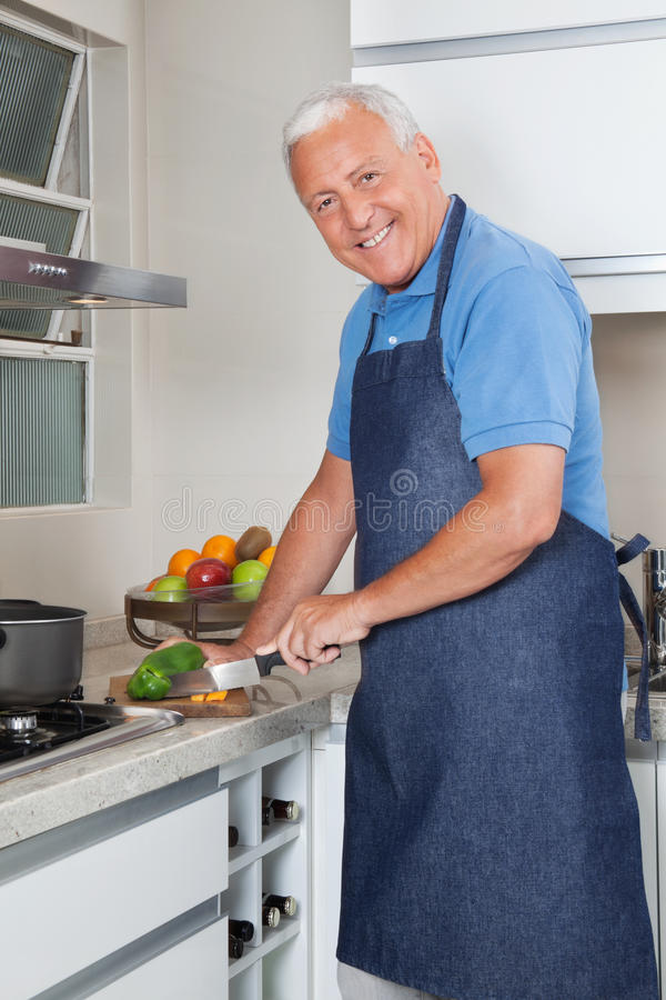Senior Man Cutting Vegetables. Portrait of smiling senior man cutting vegetables at kitchen counter stock image