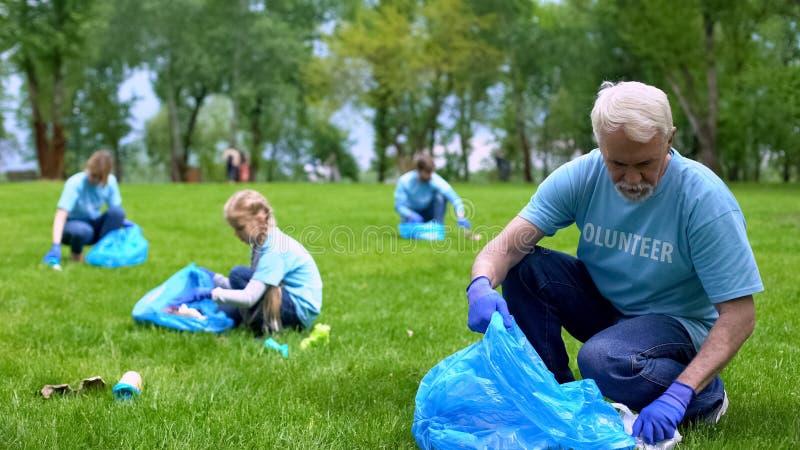 Senior man die afval oppikt in het park samen met familie glimlach camera, aardezorg stock afbeelding