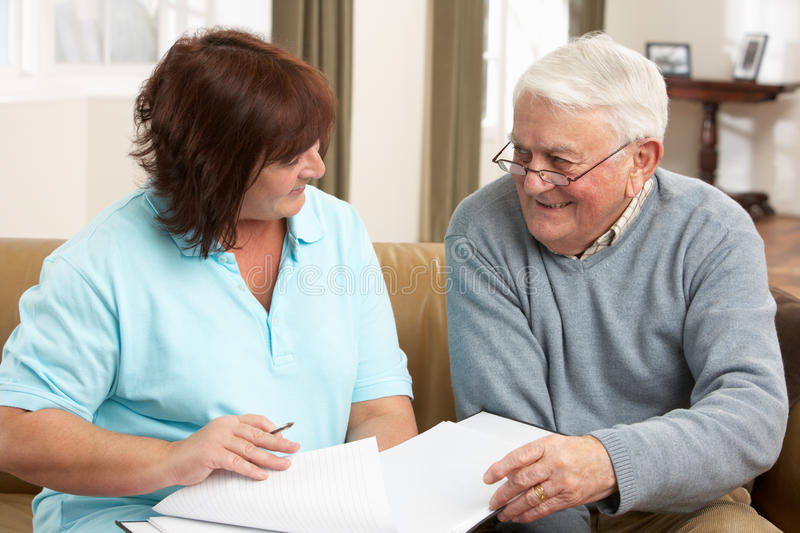 Senior Man In Discussion With Health Visitor At Ho. Me Smiling royalty free stock photography