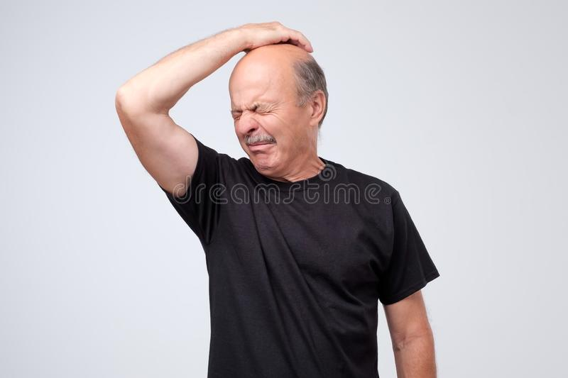 Senior man with disgust on his face sniffing something stinking, very bad smell isolated on gray background. stock photos