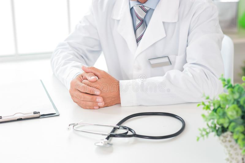 Senior doctor at his office in hospital working close-up sitting still. Senior man doctor at his office in clinic close-up sitting still palms together in a lock royalty free stock images