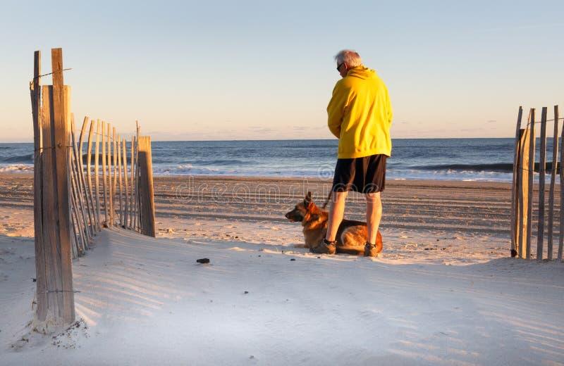 Senior Man with Dog Enjoying Morning on North Carolina Beach royalty free stock photography