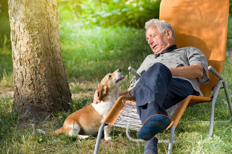 Senior man with dog. Senior man sitting in sunbed in park and cuddling cute dog royalty free stock photo