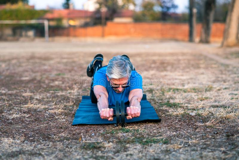 Senior man doing abs exercise. With a roller royalty free stock photography