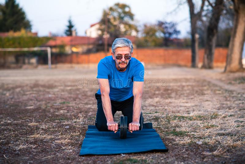 Senior man doing abs exercise. With a roller royalty free stock image