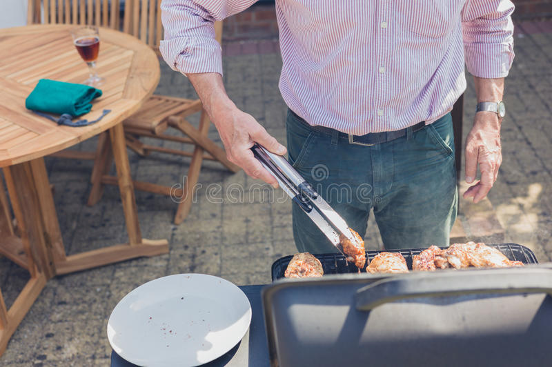 Senior man doing barbecue in garden. A senior man is attending to a barbecue in the garden on a sunny day stock image