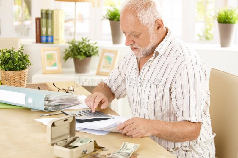 Senior man doing calculation at home. Senior man busy doing calculation, counting money and bills at home, sitting at desk stock image
