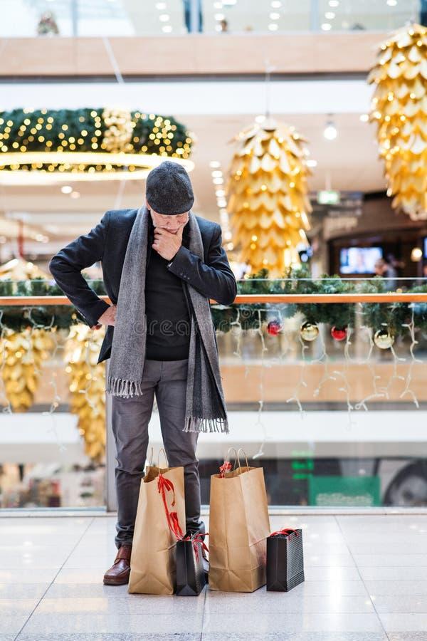 Thoughtful senior man with flat cap doing Christmas shopping. royalty free stock image