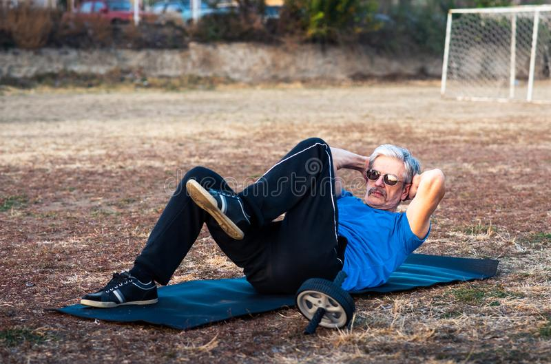 Senior man doing crunches for outdoors workout stock photography