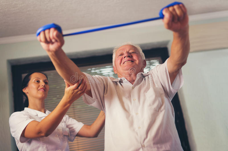 Senior man doing exercises using a strap. Senior men doing exercises using a strap to extend and strenthen her neck and shoulder muscles stock photography