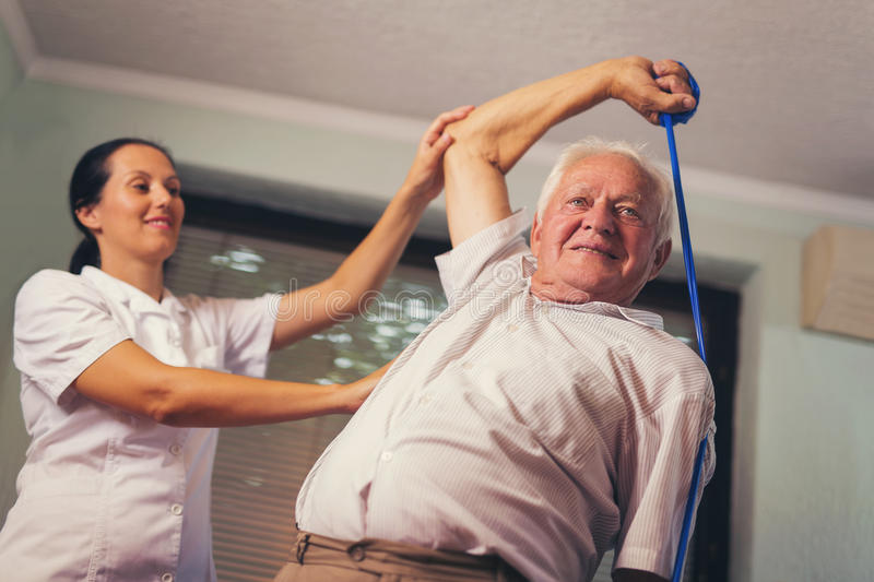 Senior man doing exercises using a strap. Senior men doing exercises using a strap to extend and strenthen her neck and shoulder muscles stock image