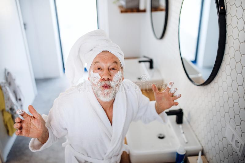 A senior man doing morning routine in bathroom indoors at home. stock photography