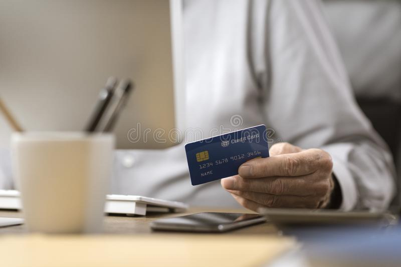 Senior man doing online shopping with a credit card royalty free stock photos