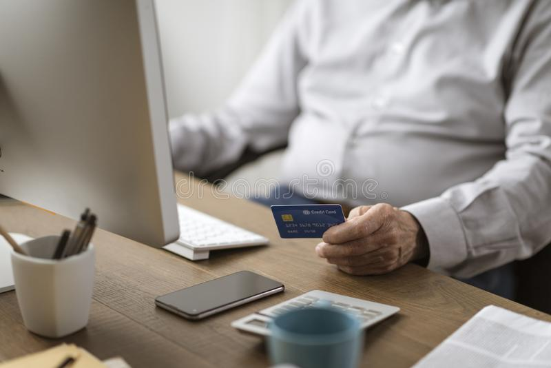 Senior man doing online shopping with a credit card royalty free stock photography