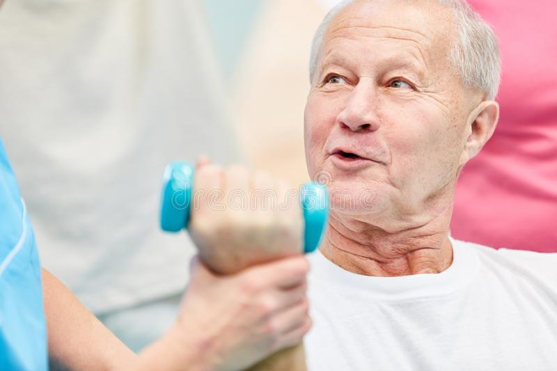 Senior man doing an exercise with dumbbells. Senior man doing a rehab exercise with dumbbells in the course for physiotherapy royalty free stock photos