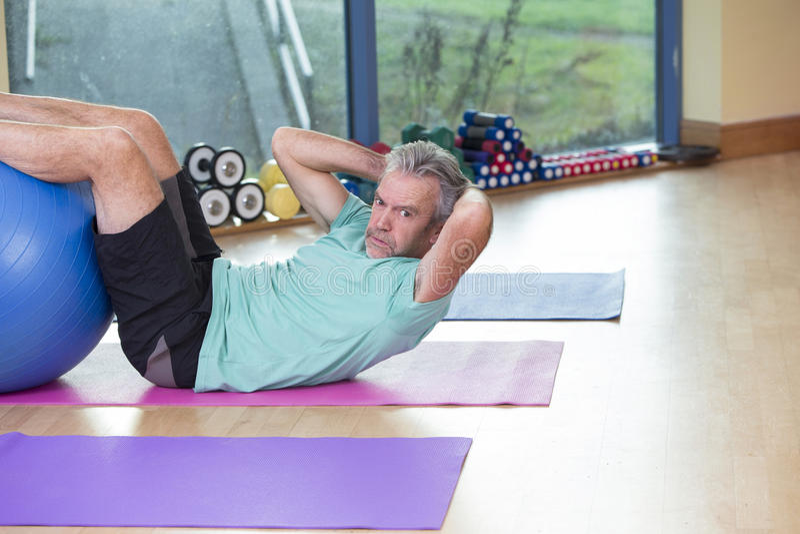 Senior man doing sit-ups at the gym royalty free stock photo
