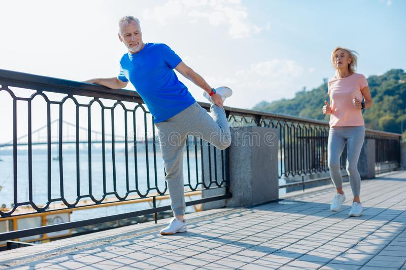 Senior man doing stretching exercises while woman jogging royalty free stock images