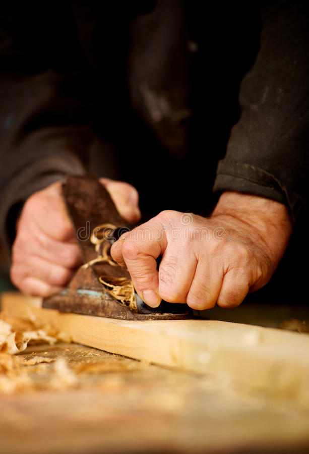 Senior man doing woodworking. Senior man or carpenter doing woodworking planing the surface of a plank of wood in his workshop with a manual plane as he enjoys stock images