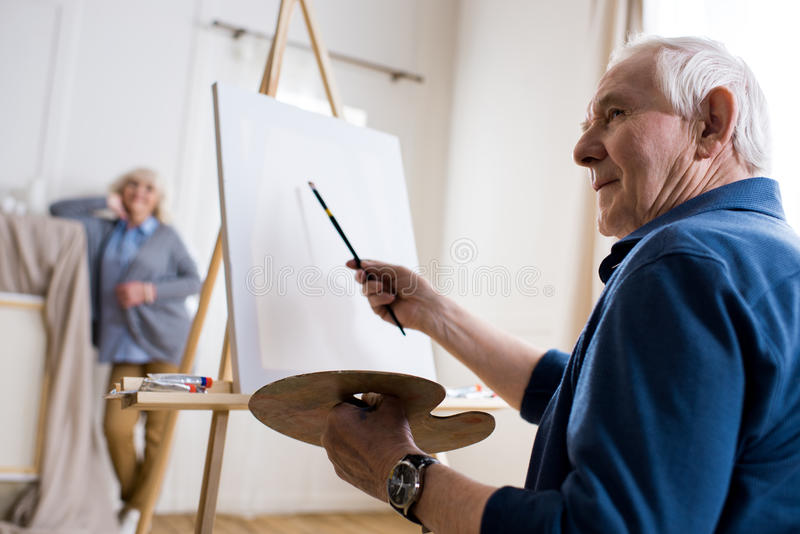 Senior man drawing portrait of woman in art workshop royalty free stock photo