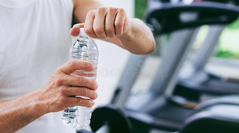 Senior man drink mineral water in fitness center royalty free stock photos