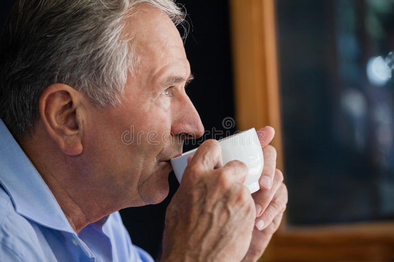 Senior man drinking coffee at cafe shop royalty free stock images