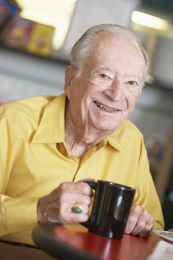 Senior man drinking hot beverage royalty free stock image