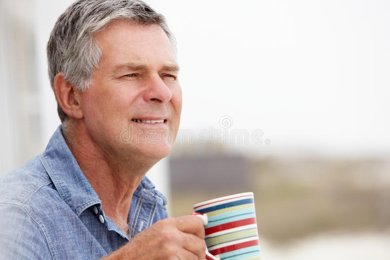Senior man drinking tea outdoors. Looking off camera royalty free stock photos