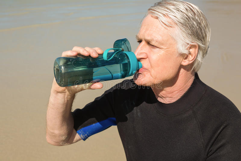 Senior man drinking water while sitting at beach royalty free stock photos