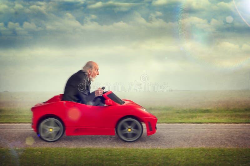 Senior man driving a toy racing car stock photo