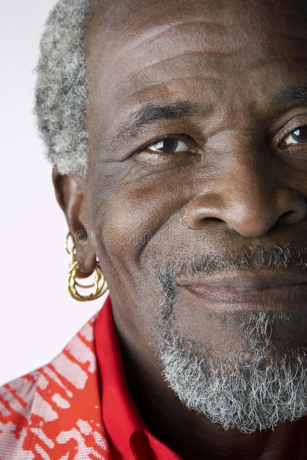 Senior Man With Earrings. Closeup portrait of a senior African American man with earrings against white background stock photo