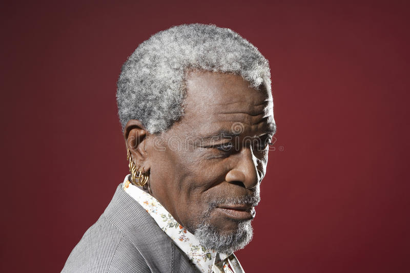 Senior Man With Earrings. Closeup side view of a senior African American man with earrings against red background stock photos