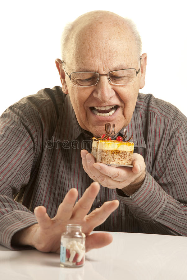 Senior man eating a cake. While hiding a bottle of pills, isolated on white stock images