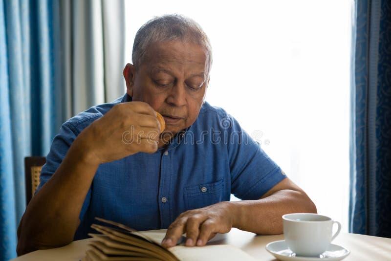 Senior man eating food while reading book in nursing home stock image